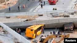Petugas penyelamat mencoba mengeluarkan kendaraan-kendaraan yang terjebak di bawah jembatan penyeberangan yang ambruk saat sedang dibangun di Belo Horizonte, Brazil (3/7).