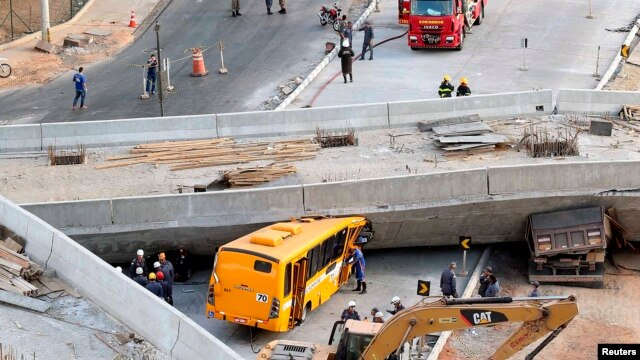 Rescue workers try to reach vehicles trapped underneath an overpass bridge that collapsed while under construction in Belo Horizonte, Brazil, July 3, 2014.