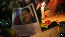 A woman places a candle in front of an image of Venezuela's President Hugo Chavez outside the Venezuela's embassy in La Paz, Bolivia, March 5, 2013.