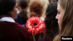 A student holds a flower during a vigil to commemorate victims of Friday's shooting, outside Masjid Al Noor mosque in Christchurch, New Zealand March 18, 2019.