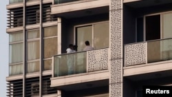 A policeman takes a photo on the balcony of a unit in which two women's bodies were found in a flat at Hong Kong's Wanchai district Nov. 1, 2014.