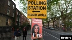 A Pro-Choice poster featuring Savita Halappanavar is placed near a sign for a polling station ahead of a May 25 referendum on abortion law, in Dublin, Ireland, May 23, 2018.