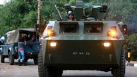 A armored military vehicle drives from the Westgate shopping center after an exchange of gunfire. Sept. 23, 2013.