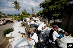 FILE - Men belonging to the Self-Defense Council of Michoacan ride on a sandbag-filled truck while trying to flush out alleged members of The Caballeros Templarios drug cartel from the town of Nueva Italia, Mexico, Jan. 12, 2014.