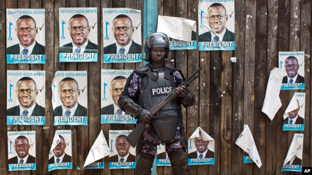 A Ugandan riot policeman blocks the gate of the party headquarters of opposition leader Kizza Besigye, shortly after raiding the premises for the second time in a week, in the capital Kampala, Feb. 22, 2016.
