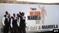 Grupa učenika ispred postera na kojem je najavljen Dan Neslona Mandele, Johanesburg, 17. juli, 2011.