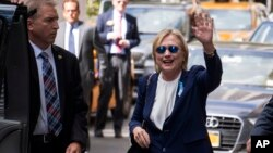 Democratic presidential candidate Hillary Clinton waves as she walks from an apartment building, Sept. 11, 2016, in New York.