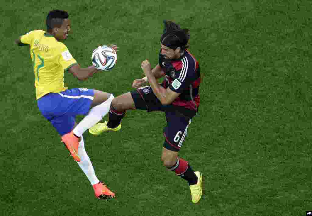 Brazil's Luiz Gustavo and Germany's Sami Khedira go for the ball during the World Cup semifinal soccer match between Brazil and Germany at the Mineirao Stadium in Belo Horizonte, Brazil, July 8, 2014.