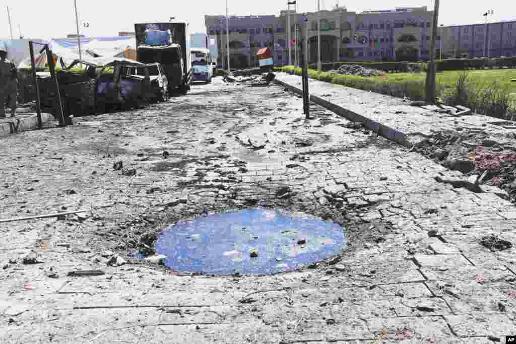 This photo provided by Yemen's Defense Ministry shows a crater and damaged vehicles after an explosion at the Defense Ministry complex in Sana'a, Dec. 5, 2013.