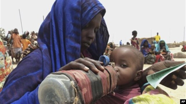A mother quenches her malnourished child's thirst while waiting for food handouts at a health center in drought-stricken remote Somali region of Ethiopia, July 9, 2011.