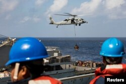 Sailors aboard the amphibious assault ship USS Kearsarge (LHD 3) observe as an MH-60 Sea Hawk helicopter transfers pallets of supplies from the fast combat support ship USNS Supply (T-AOE 6) during replenishment-at-sea for continuing operations.