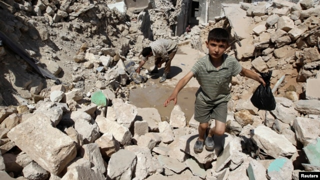 A boy walks on the rubble of buildings damaged by what activists said were missiles fired by Syrian Air Force fighter jets loyal to President Bashar al-Assad in Salqin city, Idlib governate, May 28, 2013.