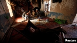 An ethnic Hazara child sleeps as the rest of the family eat a meal in their home in Turkman camp in Nowshera, Pakistan.