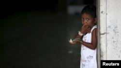 A young Rohingya migrant who arrived in Indonesia last week by boat eats a snack at a temporary shelter in Aceh Timur regency near Langsa in Indonesia's Aceh Province, May 26, 2015.