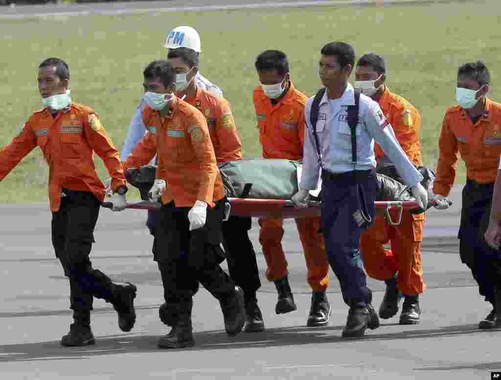 National Search and Rescue Agency (BASARNAS) personnel carry the body of a victim on board the ill-fated AirAsia Flight 8501, from a helicopter upon arrival at the airport in Pangkalan Bun, Indonesia, Jan. 1, 2015.