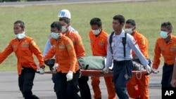 Personel Basarnas menggotong jasad korban pesawat AirAsia penerbangan 8501, yang baru tiba dari helikopter di bandara Pangkalan Bun, Kamis (1/1).