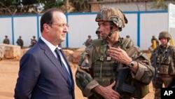 Le président français François Hollande, à gauche, en pleine discussion avec des hommes des troupes françaises à Bangui, en République centrafricaine, 28 février 2014. (AP Photo / Frederic Lafargue)