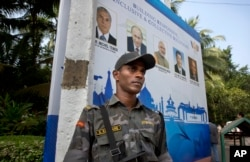 A Goa police commander stands guard near the banner of BRICS summit in Goa, India, Friday, Oct. 14, 2016.