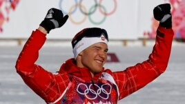 Winner Switzerland's Dario Cologna celebrates during a flower ceremony for the men's 15 km cross-country classic event at the Sochi 2014 Winter Olympic Games in Rosa Khutor, Feb. 14, 2014.