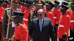 FILE - Sudan's then-President Omar al-Bashir inspects the guard of honor upon his arrival in Entebbe, Uganda, Nov. 13, 2017. Uganda says it will consider giving asylum to the deposed leader.