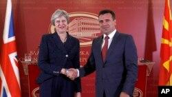 Perdana Menteri Inggris Theresa May (kiri) berjabat tangan dengan mitranya dari Macedonia, Perdana Menteri Zoran Zaev (kanan), menyusul pertemuan antara kedua pemimpin di Skopje, Macedonia, Kamis 17 Mei 2018.