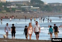 Turis berjalan di pantai saat pemerintah memperpanjang pembatasan untuk mengekang penyebaran COVID-19 di Badung, Bali, 9 September 2021. (Foto Antara/Nyoman Hendra Wibowo/via REUTERS)