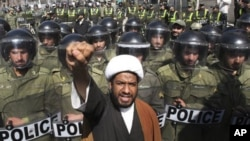 A Bahraini Shi'ite cleric chants slogans in a protest against Saudi and Bahraini leaders in front of the Saudi Embassy in Tehran, as Iranian police officers protect the Embassy, Iran, March 17, 2011