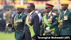Emmerson Mnangagwa, second left, with Army General Constantino Chiwenga, second right, inspects the military parade after being sworn in as President at the presidential inauguration ceremony in the capital Harare, Zimbabwe Friday, Nov. 24, 2017. Mnangagwa is being sworn in as Zi