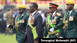 FILE: Emmerson Mnangagwa, second left, with Army General Constantino Chiwenga, second right, inspects the military parade after being sworn in as President at the presidential inauguration ceremony in the capital Harare, Zimbabwe Friday, Nov. 24, 2017.