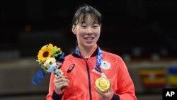 Petinju Jepang Sena Irie, berdiri dengan Medali Emasnya setelah mengalahkan Nesthy Petecio dari Filipina, dalam pertandingan final tinju kelas bulu 60 kg putri pada Olimpiade Musim Panas 2020 di Tokyo, Jepang, Selasa, 3 Agustus 2021. (AP Photo/Luis ROBAYO, Kolam Renang)