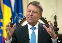 FILE - Romanian President Klaus Iohannis speaks with an AP reporter at the Cotroceni Palace in Bucharest, Romania, Feb. 8, 2017.