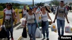 Người dân Venezuela xách những túi nhu yếu phẩm mua được từ Colombia, ở San Antonio del Tachira, Venezuela, 10/7/2016.