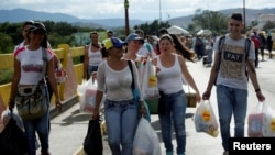 Venezuelan citizens are seen carrying bags as they cross the Colombian-Venezuelan border over the Simon Bolivar international bridge, after shopping and taking advantage of the temporary border opening in San Antonio del Tachira, Venezuela, July 10, 2016.