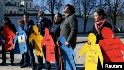 FILE - Activists take part in a flashmob to highlight human rights violations against Tatars living in Russia-annexed, in Kyiv, Ukraine, March 16, 2016.