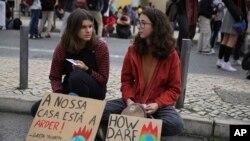 آب و ہوا کی تبدیلیوں کے خلاف جمعے کے روز دنیا بھر میں مظاہرے ہوئے۔ لسبن میں مظاہرے میں شامل دو خواتین ایک پارک میں بینر لیے بیٹھی ہیں۔ 29 نومبر 2019