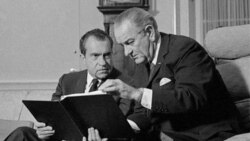 In this 1968 black-and-white file photo, President Lyndon Johnson, right, confers with President-elect Richard Nixon in the White House in Washington