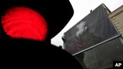 英国工人在伦敦前卫艺术展览馆里森艺术馆外悬挂两层楼高的艾未未黑白照片,为艾未未的艺术展做准备。 (资料照片 2011年5月11日)
