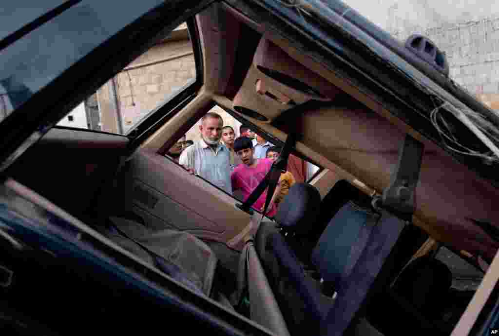 Pakistani residents investigate damages of a vehicle caused by a bomb explosion early morning in Karachi, Pakistan, August 7, 2013.