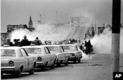 FILE - Tear gas fumes fill the air as state troopers, ordered by Gov. George Wallace, break up a demonstration march in Selma, Ala., on what is known as Bloody Sunday on March 7, 1965.
