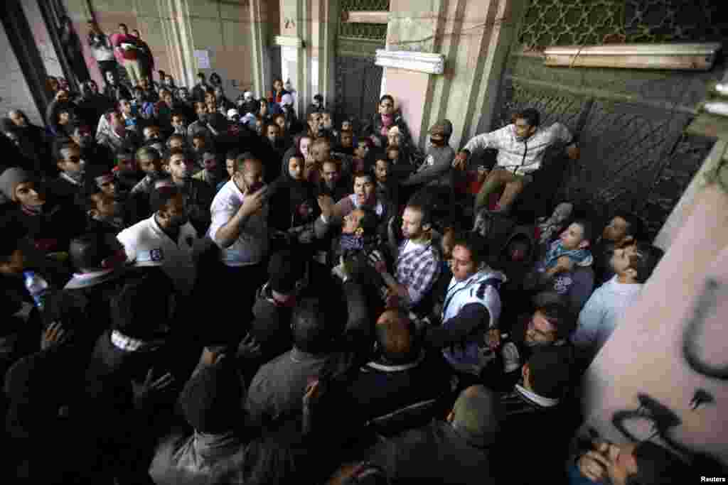 People clash with anti-Morsi protesters, after the protesters blocked the gate of a government building near Tahrir Square in Cairo, Egypt, December 11, 2012.