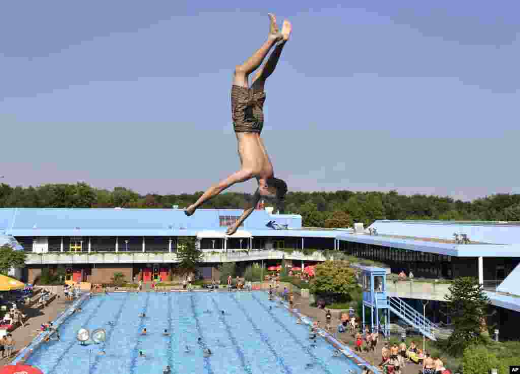 A boy jumps into a public pool on a hot day in Gelsenkirchen, Germany.
