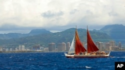 FILE - The Hokulea sailing canoe is seen off Honolulu, April 29, 2014. The Polynesian voyaging canoe is returning to Hawaii after a three-year journey around the world guided only by nature with navigators using no modern navigation to guide them.
