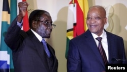 FILE: Zimbabwe's President Robert Mugabe (L) gestures as South Africa's President Jacob Zuma looks on at the end of a press briefing at the Union building in Pretoria, April 8, 2015.