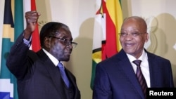 FILE - Zimbabwe's President Robert Mugabe (L) gestures as South Africa's President Jacob Zuma looks on at the end of a press briefing at the Union building in Pretoria, April 8, 2015.