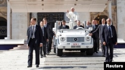 Pope Francis waves as he leaves after leading the weekly audience in Saint Peter's Square at the Vatican, Oct. 2, 2013.