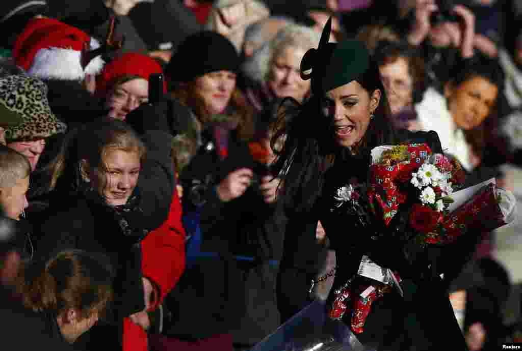 A Princesa Kate do Reino Unido corre para receber as flores do povo que espera por ela à saída da missa de Natal na Igreja de Sandringham em Norfolk, Inglaterra.