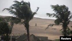 Seorang warga berjalan di pinggir pantai di Gopalpur di distrik Ganjam, Odisha, India (12/10).
