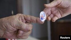 """Một nhân viên phòng phiếu trao một miếng dán nhỏ có dòng chữ """"Tôi đã bầu"""" cho một cử tri ở Stillwater, Oklahoma, hôm 1/3."""