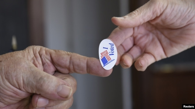 A poll worker hands a sticker to a voter on Super Tuesday in Stillwater, Okla., March 1, 2016.
