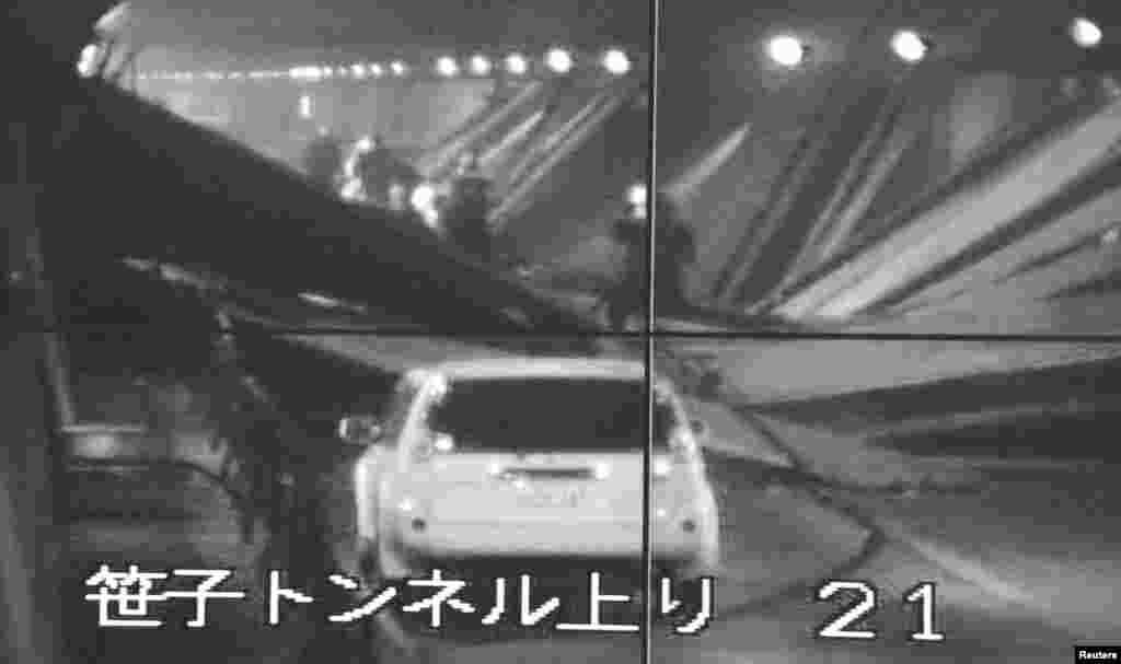 Màn hình theo dõi sinh hoạt trong hầm cho thấy một chiếc xe và một toan nhân viên cấp cứu trong đường hầm Sasago. (Kyodo)